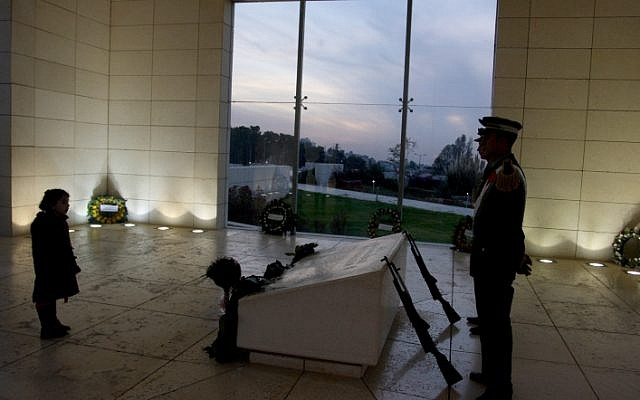 A Palestinian girl standing next to the grave of the late Palestinian leader Yasser Arafat in the West Bank town of Ramallah, as Palestinian security guards stand by,  November 2011. (photo credit: Issam Rimawi/ Flash90)