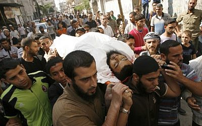 Palestinian mourners carry the body of Mohammed Sheikh, 23, killed by an Israeli air strike on Gaza on Wednesday, Oct. 24 (photo credit: Abed Rahim Khatib/Flash90)