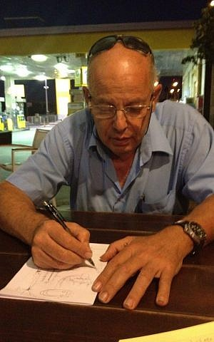 Israel Asaf, sketching the battle on a piece of paper (Photo credit: Mitch Ginsburg/ Times of Israel)