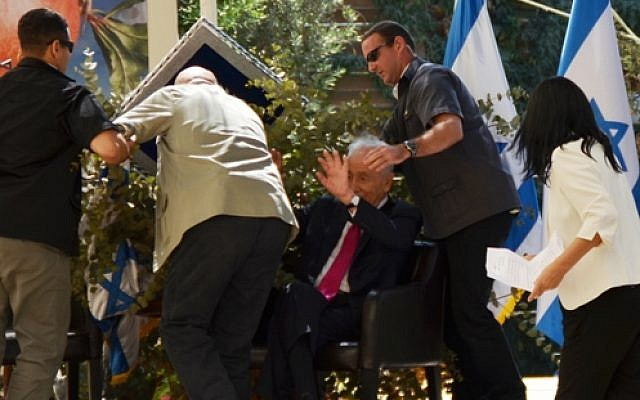 President Peres's bodyguards remove a sign that fell on him (photo credit: Sharon Marks Altshul)
