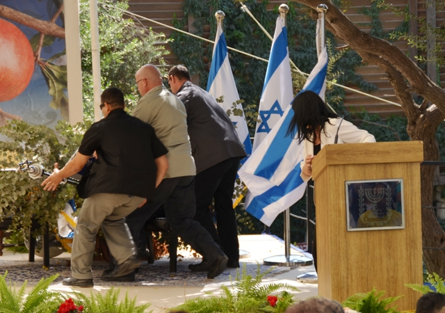President Peres' bodyguards hurry to his rescue after a sign fell on him Wednesday (photo credit: Sharon Marks Altshul)