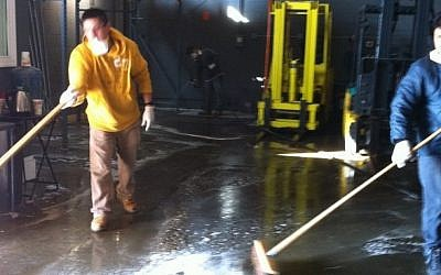 Workers clean and sanitize the warehouse of the kosher cheese firm Anderson International Foods in Jersey City, NJ. (Chavie Lieber/JTA)