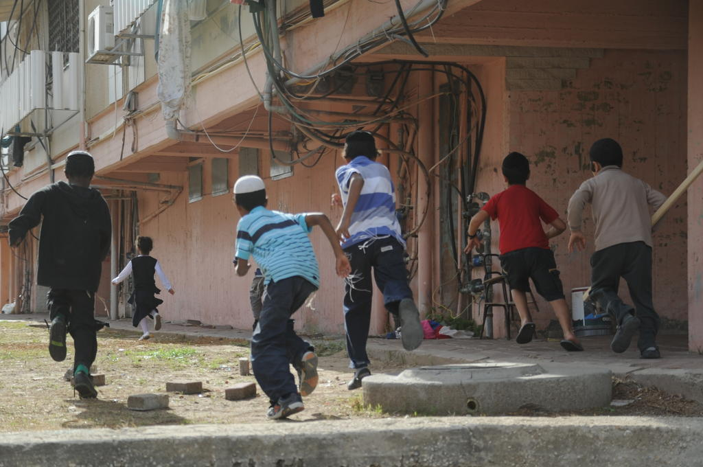 Children in Kiryat Malachi run toward a bomb shelter Friday. A residential building in the southern city was hit by a rocket Thursday, killing three. (photo credit: IDF Spokesperson)