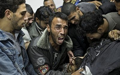 A Palestinian man cries next the body of a dead relative in the morgue of Shifa Hospital in Gaza City on Sunday (photo credit: AP/Bernat Armangue)