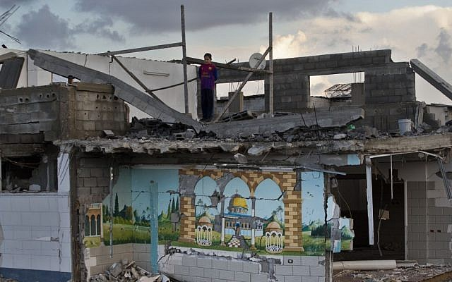 A Palestinian boy looks out from the rooftop of a destroyed house in Gaza City on Sunday (photo credit: AP/Bernat Armangue)