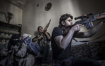 A rebel sniper aims at Syrian army positions in the Aleppo Jedida district in Syria last week. (Photo credit: AP/Narciso Contreras)