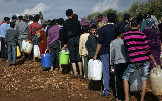 Syrian refugees line up to fill plastic containers with water at a displaced persons camp near the Turkish border, November 2012 (photo credit: AP/Khalil Hamra/File)
