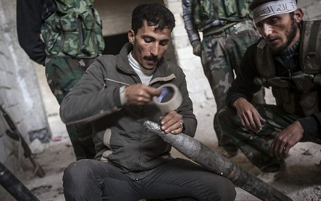Syrian rebels prepare to fire a homemade rocket as they carry out a coordinated attack on a Syrian air force compound on the outskirts of Aleppo Last month (photo credit: AP/Narciso Contreras)