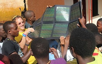Yosef Abramowitz (left) and youthful residents of the Agahozo-Shalom Youth Village hold a solar panel. (Photo credit: Courtesy)