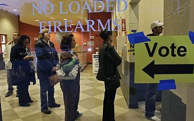 Behind a sign barring loaded firearms in the building, people stand in line to cast their votes on Election Day at a precinct at the Wake County Firearms Education and Training Center in Apex, N.C.,  Nov. 6, 2012. (AP Photo/Gerry Broome)