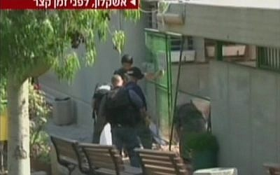 Police inspect the damage to an Ashkelon school caused by a rocket fired from Gaza (screen capture/Channel 2)