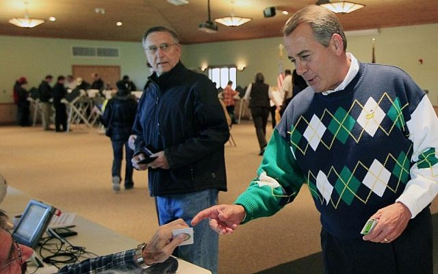 Speaker John Boehner presents his ID at a polling station in Ohio, Tuesday (photo credit: Al Behrman/AP)