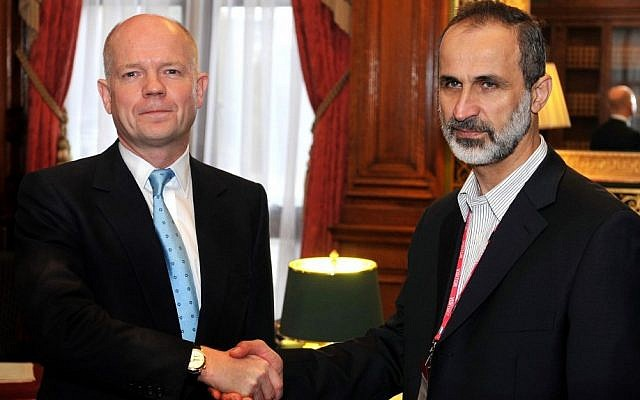 Britain's Foreign Secretary William Hague shakes hands for the cameras with head of the new Syrian National Coalition for Opposition and Revolutionary Forces Mouaz al-Khatib before a meeting on the continuing conflict in Syria on Friday Nov. 16 (photo credit: AP/John Stillwell)
