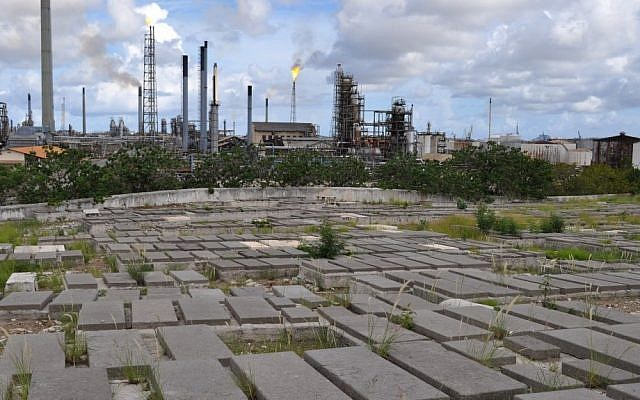 Graves at the Beth Haim cemetery on the outskirts of Willemstad, Curacao, are backdropped by the Isla oil refinery (photo credit: AP/Karen Attiah)