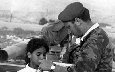 Sgt. Eliezer Sheffer shares water with Basima Shafiq before delivering her home to Jerusalem in June 1967. (Courtesy of Aharon Zukerman/JTA)