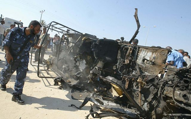 Members of the Hamas executive inspect the destroyed vehicle of Islamic Jihad Movement military leader Omar al-Khati after it was targeted in an Israeli air strike, July 2007 (photo credit: Ahmad Khateib/Flash90)