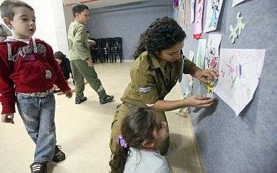 Illustrative. An IDF soldier plays with children in a bomb shelter in southern Israel in November 2012. (Miriam Alster/Flash 90)