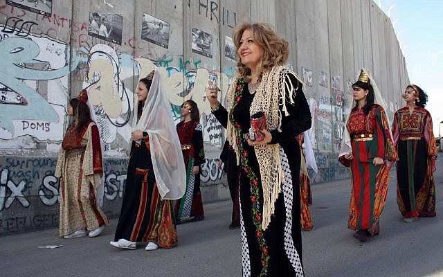 Palestinian Christian women wearing traditional clothes walk past the Israeli separation barrier or wall in the West Bank town of Bethlehem, as Christmas approaches, on December 23, 2010. (photo credit: Najeh Hashlamoun/Flash90)