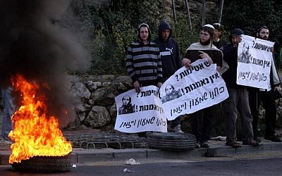 Illustrative: Youth aligned with the settler movement burning tires in Jerusalem in 2012 to protest an outpost demolition. (Abir Sultan/ Flash90)