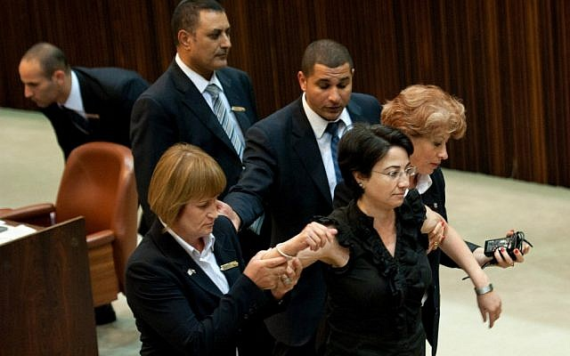 Arab MK Hanin Zoabi (Balad) is escorted  out of a plenum session by Knesset staff, July 13, 2011 (photo credit: Omer Miron/Flash90)