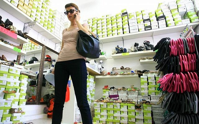 A woman talking on the phone while shopping for shoes on Shenkin Street in Tel Aviv (photo credit: Chen Leopold/Flash90)