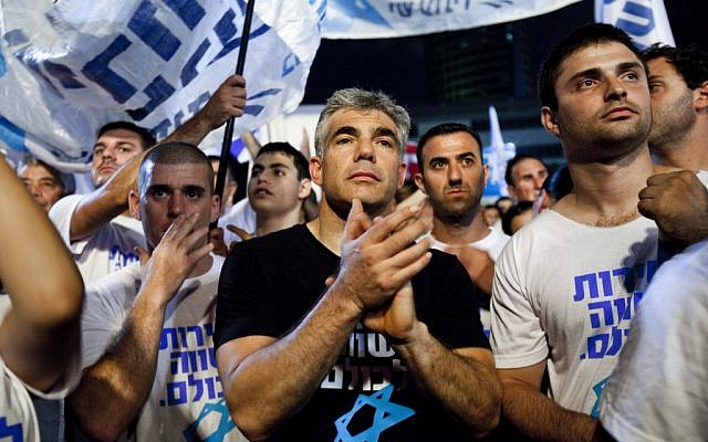 Ex-TV anchor and Yesh Atid party leader Yair Lapid joins some 25,000 people at a rally in Tel Aviv in July urging the government to enact universal draft legislation. (photo credit: Tali Mayer/Flash90)