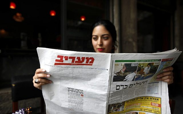 A woman reads a copy of the daily newspaper Maariv (photo credit: Miriam Alster/Flash90)