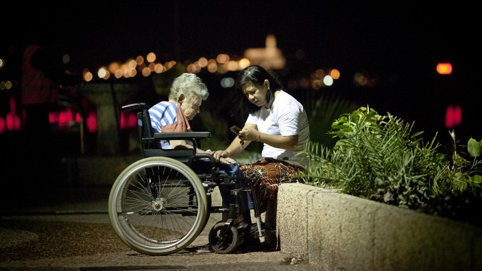 A Filipina caretaker with an elderly Israeli woman on the Tel Aviv boardwalk (photo credit: Moshe Shai/Flash90/File)