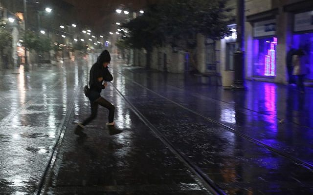 An Israeli woman runs for cover as the first rain of the year falls on Jerusalem on Friday (photo credit: Oren Nahshon/Flash90)