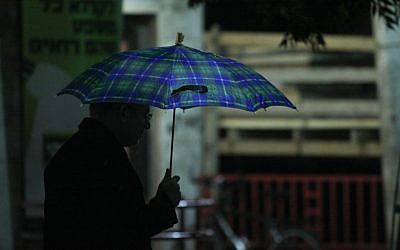 A Jerusalem man takes cover from the rain on Friday night. (photo credit: Oren Nahshon / FLASH90)