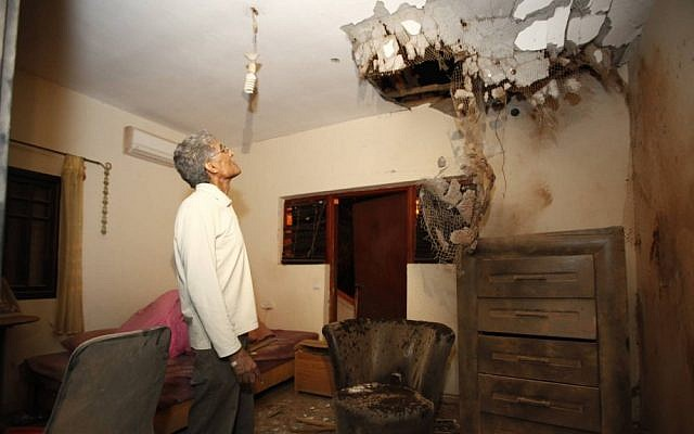An Israeli man examines the damage caused to a house in Sderot by a Kassam rocket fired from the Gaza Strip on Sunday (photo credit: Edi Israel/Flash90)
