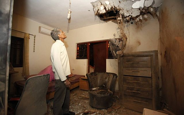 An Israeli man examines the damage to his daughter's bedroom after a Kassam rocket fired by Palestinian terrorists from Gaza hit his house in the southern town of Sderot on November 11 (photo credit: Edi Israel/Flash90)