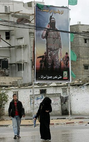 Palestinians walk next to past murals depicting slogans for Hamas in the Rafah refugee camp on Monday.(photo credit: Abed Rahim Khatib/Flash 90)