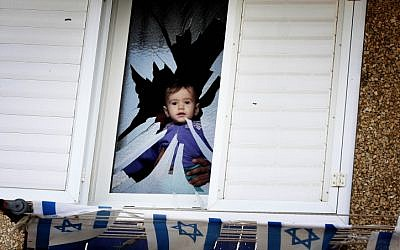 A father and his baby look out the shattered window of their house that was hit by shrapnel from a Grad rocket that landed in Netivot on Monday,  November 12 (photo credit: Edi Israel/Flash90)