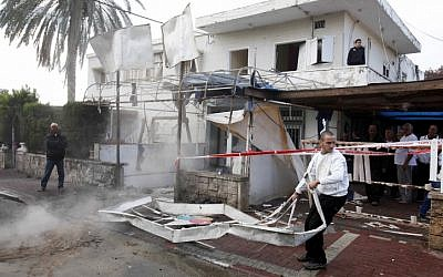 A citizen clears away wreckage caused by a Grad rocket hitting a house in Netivot on Monday, November 12 (photo credit: Edi Israel/Flash90)