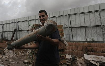 An Israeli holds the remnants of a rocket, fired by Palestinian terrorists, in the southern town of Netivot, Monday, November 12, 2012 (photo credit: Tsafrir Abayov/Flash90)