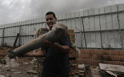 A Netivot resident holds the remains of a rocket, fired by Palestinian militants in Gaza, on Monday, Nov. 12, 2012. (photo credit: Tsafrir Abayov/Flash90)