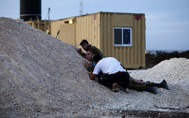 Illustrative: Israeli soldiers and citizen takes cover as a siren sounds warning of incoming rockets in Ashdod  (Photo credit: Dima Vazinovich/Flash90)