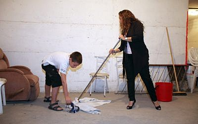 A Tel Aviv mother and her son clean a municipal shelter in the city on November 16, 2012. after a rocket was fired on the region for the second time in the last two days (photo credit: Gidon Markowicz/Flash90)