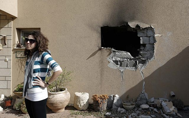 An Israeli woman stands outside a house damaged by a rocket fired from the Gaza Strip on Friday, Nov. 16 (photo credit: Tsafrir Abayov/Flash90)