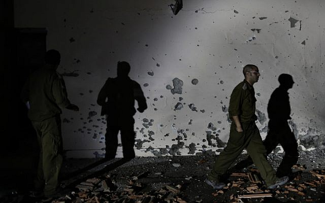Soldiers examine a damaged wall of a house in the Be'er Tuvia region that was hit by a rocket fired from the Gaza Strip on Friday, Nov. 16 (photo credit: Tsafrir Abayov/Flash90)
