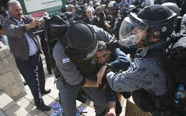 Israeli policemen arrest a Palestinian man during a demonstration in support of the people of Gaza and against Israel's military operations in the Strip, at the Damascus Gate in Jerusalem's Old City on Friday. (photo credit: Yonatan Sindel/Flash90)