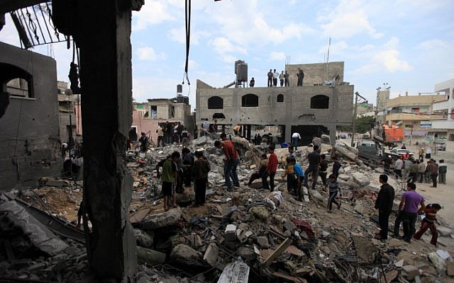 Palestinians view the rubble of a destroyed home after Israeli air force rockets hit a Hamas official's house in the northern Gaza Strip on 17 November 2012. (photo credit: Wissam Nassar/Flash90)