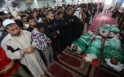 Palestinian mourners in Gaza pray over five bodies, draped in Hamas flags, of people who were killed by an Israeli air strike, November 17 (photo credit: Wissam Nassar/Flash90)
