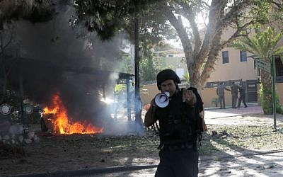 A police officer shoos away onlooker coming to view a vehicle that caught fire after suffering a hit by a rocket fired from Gaza, in Ashkelon, on Sunday, November 18 (photo credit: Yossi Zamir/Flash90)