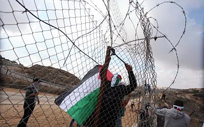 Palestinians cut through the fence along the 443 highway (photo credit: Issam Rimawi/Flash90)