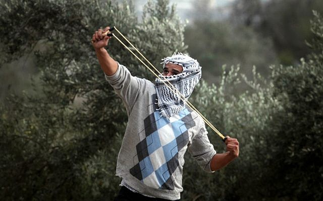 A Palestinian student from the Birzeit University covers his face as he uses a slingshot to throw stones at Israeli troops during clashes with Israeli soldiers at the Atara checkpoint close to their university as they protest against Israel's military action on the Gaza Strip. November 19, 2012 (photo credit: Issam Rimawi/Flash90)