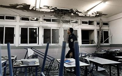 Police examine a classroom in Ashkelon damaged by rocket fire. (photo credit: Tsafrir Abayov/Flash90)