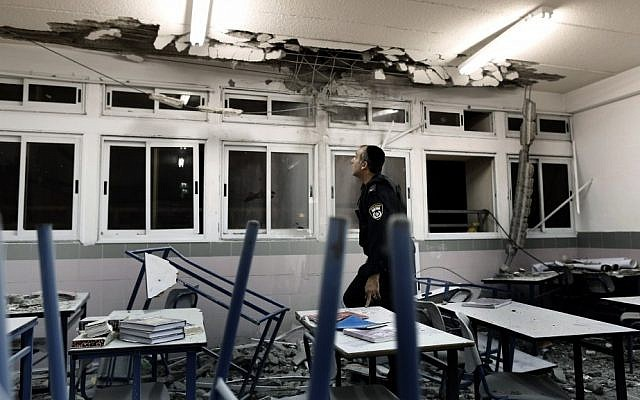 Police examine a classroom in Ashkelon damaged by rocket fire in November 2012. (photo credit: Tsafrir Abayov/Flash90)