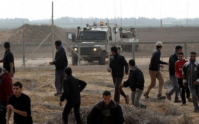 Palestinians retreat from the border fence between Israel and the southern Gaza Strip as an IDF patrol approaches in 2012. (photo credit: Abed Rahim Khatib/Flash90/File)